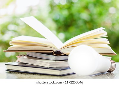 Stack of opened books with LED lamp against blurred natural green background for education concept