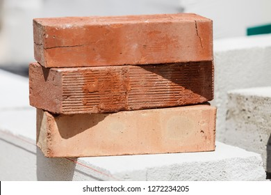 Stack of orange bricks on construction site. Renovation, building objects and details concept.