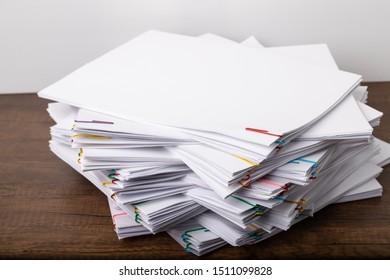 Stack of overload document paper with colorful paperclip place on wooden table, business concept footage paperless used.