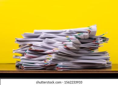 Stack overload document report paper with colorful paperclip place on yellow background, paperless business concept.