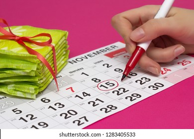 A stack of pads and a girl surrounds the days on the calendar with a red felt-tip pen when she has her menstruation, close-up, pink background