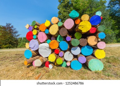 stack of painted tree trunks with various colors in park