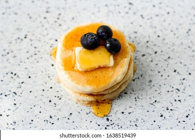 stack of pancake with three blueberries and a pat of butter dripping with syrup