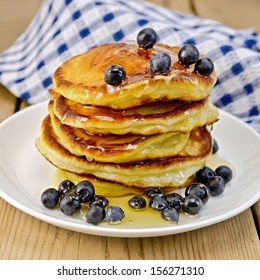 A stack of pancakes with blueberries and honey on a white plate, napkin against a wooden board