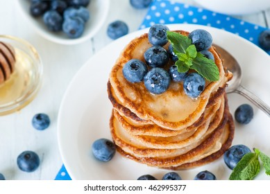 A stack of pancakes with blueberries and honey. White background.