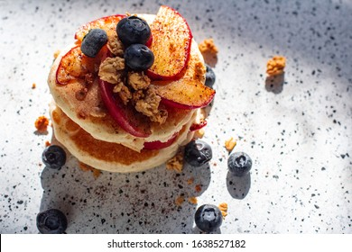 a stack of pancakes blueberries and slices of apples