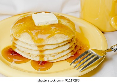 Stack of pancakes with butter, maple syrup, and fork.  Coffee in background.