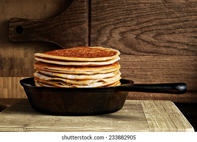stack of pancakes in a cast iron skillet on a wooden board