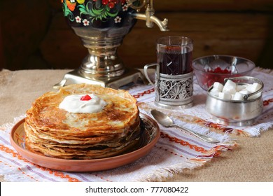 A stack of pancakes. A stack of pancakes in a clay plate and a glass of tea from a samovar on the background of a log wall.
