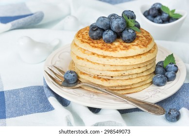 A stack of pancakes decorated with ripe berries of blueberries on the background of blue-white napkin