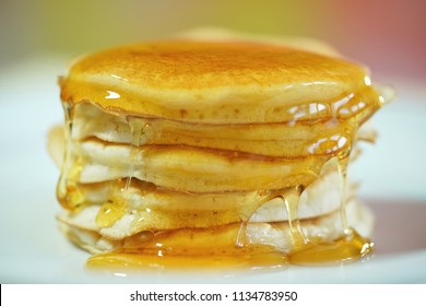 Stack of pancakes drizzled with syrup, macro closeup.