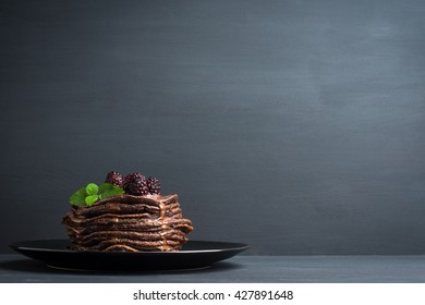 Stack of pancakes with fresh blackberries and chocolate syrup