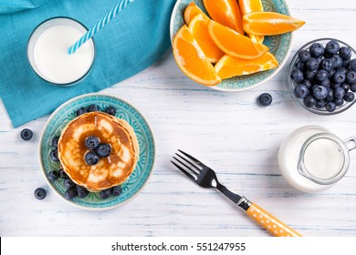 Stack of pancakes with fresh blueberry, honey, milk and orange slices, healthy breakfast concept, top view