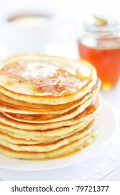 A stack of pancakes with honey