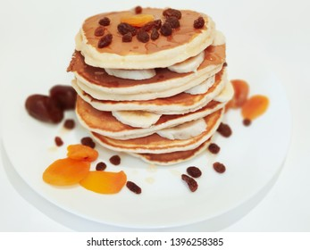 Stack of Pancakes with honey and banana on plate the Table, blur