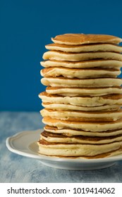 Stack of pancakes with honey on blue background