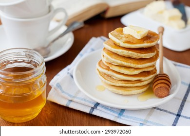 Stack of pancakes with honey syrup and butter in a white plate on a wooden rustic table with book, selective focus