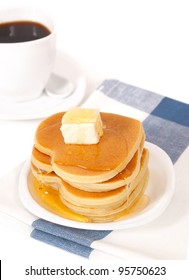 A stack of pancakes with maple syrup and butter.