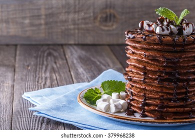 Stack of pancakes with marshmallow and chocolate syrup on dark background.