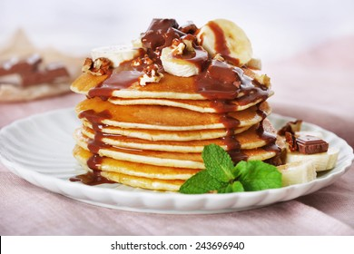 Stack of pancakes with mint, walnuts, chocolate and slices of banana on table with fabric on wooden planks background