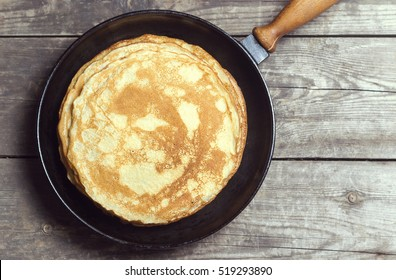 Stack of pancakes on a cast-iron frying pan. Top view. With toning