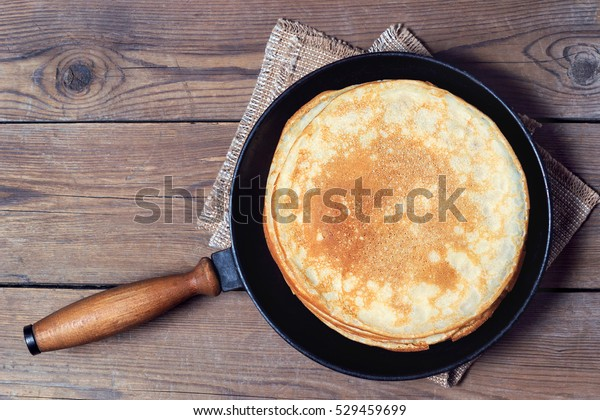 Stack of pancakes on a cast-iron frying pan. Top view. Flat lay
