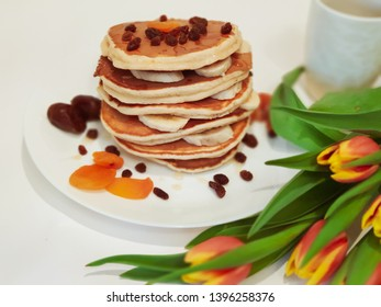 Stack of Pancakes on plate the Table with Tulips, blur