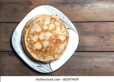 Stack of pancakes on a square plate on a wooden table. Top view. Flat lay