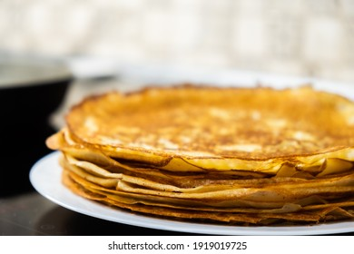 a stack of pancakes on a white plate on a kitchen background