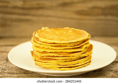 stack of pancakes on a white plate on wooden background