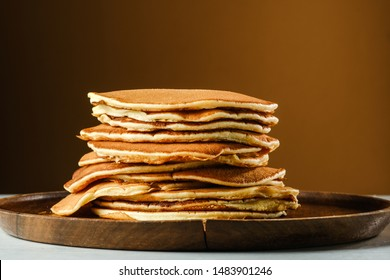 Stack of pancakes on a wooden plate. Copy space for your text.On a light brown background.