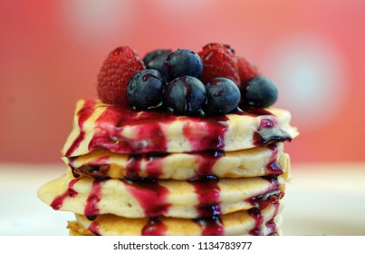Stack of pancakes with raspberries, blueberries and drizzled with blueberry maple syrup, macro closeup.