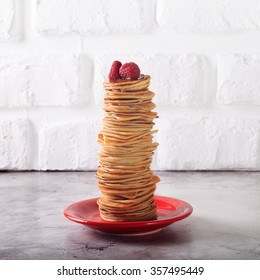 Stack of pancakes with raspberries on top. Homemade dessert. Maslenitsa concept. White brick background. Square
