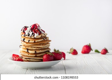 Stack of pancakes with strawberries, whip cream and chocolate syrup on a white plate on a white wooden background. Horizontal image. Copy space.