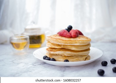 Stack of pancakes with topping, strawberry and blueberry.Placed in a white plate on a marble table and copy space.Eat with tea in the glass.