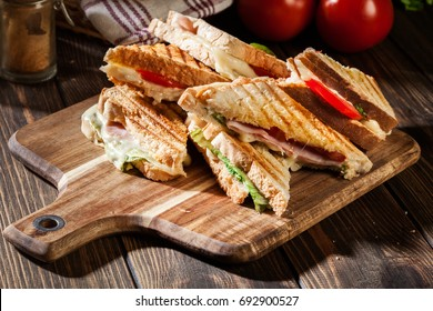 Stack of panini with ham, cheese and lettuce sandwich on a cutting board