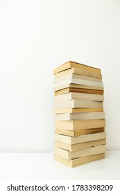 Stack of paperback books against white background with only the pages showing.