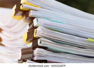 Stack of papers documents in archives files with clip papers on table at offices,  Busy offices and Pile of data unfinished folders on office desk indoor,  Business concept
