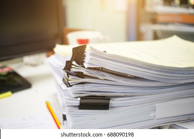 Stack of papers documents in archives files with clip papers on table at offices,  Busy offices and Pile of data unfinished folders on office desk indoor,  Business concept, vintage tone.