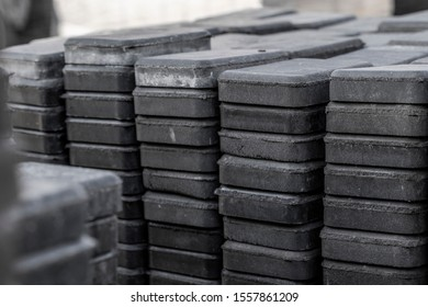 Stack of paving stone on construction site. Bricks for paving stones stacked in stacks, background texture structure. Gray pavement bricks for pavement road.