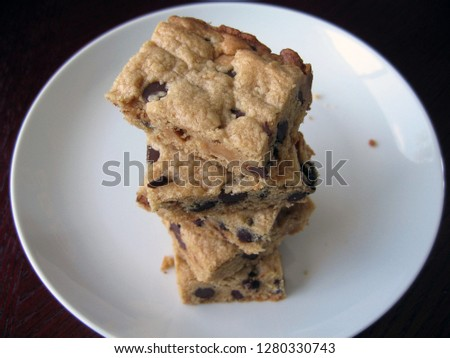 Stack of peanut butter and chocolate chip dessert bars piled on round white plate