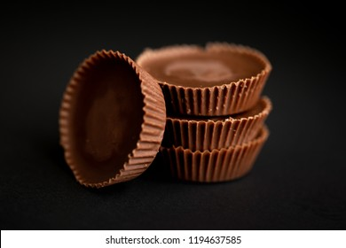 Stack of peanut butter cups on a dark black background macro