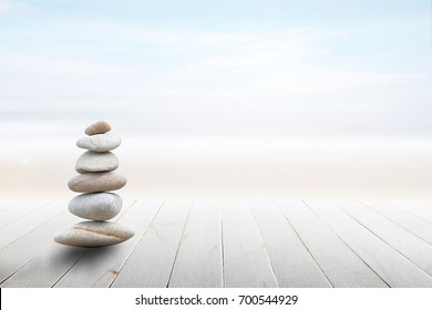 Stack of pebble stones at the beach on a wooden surface. Concept Zen, Spa, Summer, Beach, Sea, Relax.