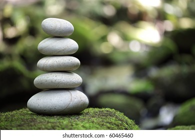 Stack of pebble stones by a stream in a forest