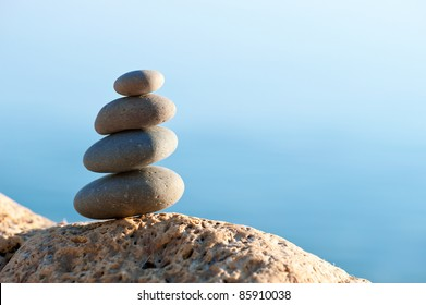 Stack of pebbles on a big rock at the beach on the blue background