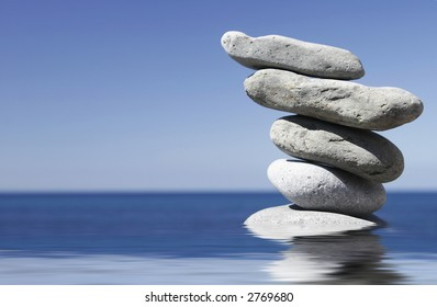 Stack of pebbles in shallow water with blue sky background