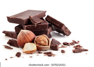 Stack of pieces of dark chocolate and hazelnuts. Isolated on white background.
