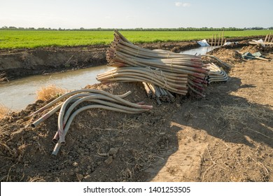 stack pile of agricultural irrigation siphons