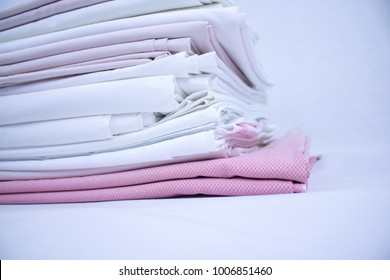 stack or pile of bed sheets, linen freshly washed and ironed, white and pink fabric, for textile retail or laundry services