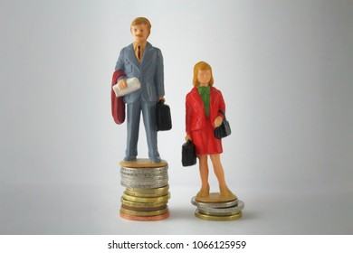 Stack pile of coins with miniature man and woman. Gender pay discrimination concept.Wage disparity between men and women theme.